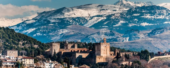 Winter view of famous Alhambra in front of Sierra Nevada mountains topped with show.
